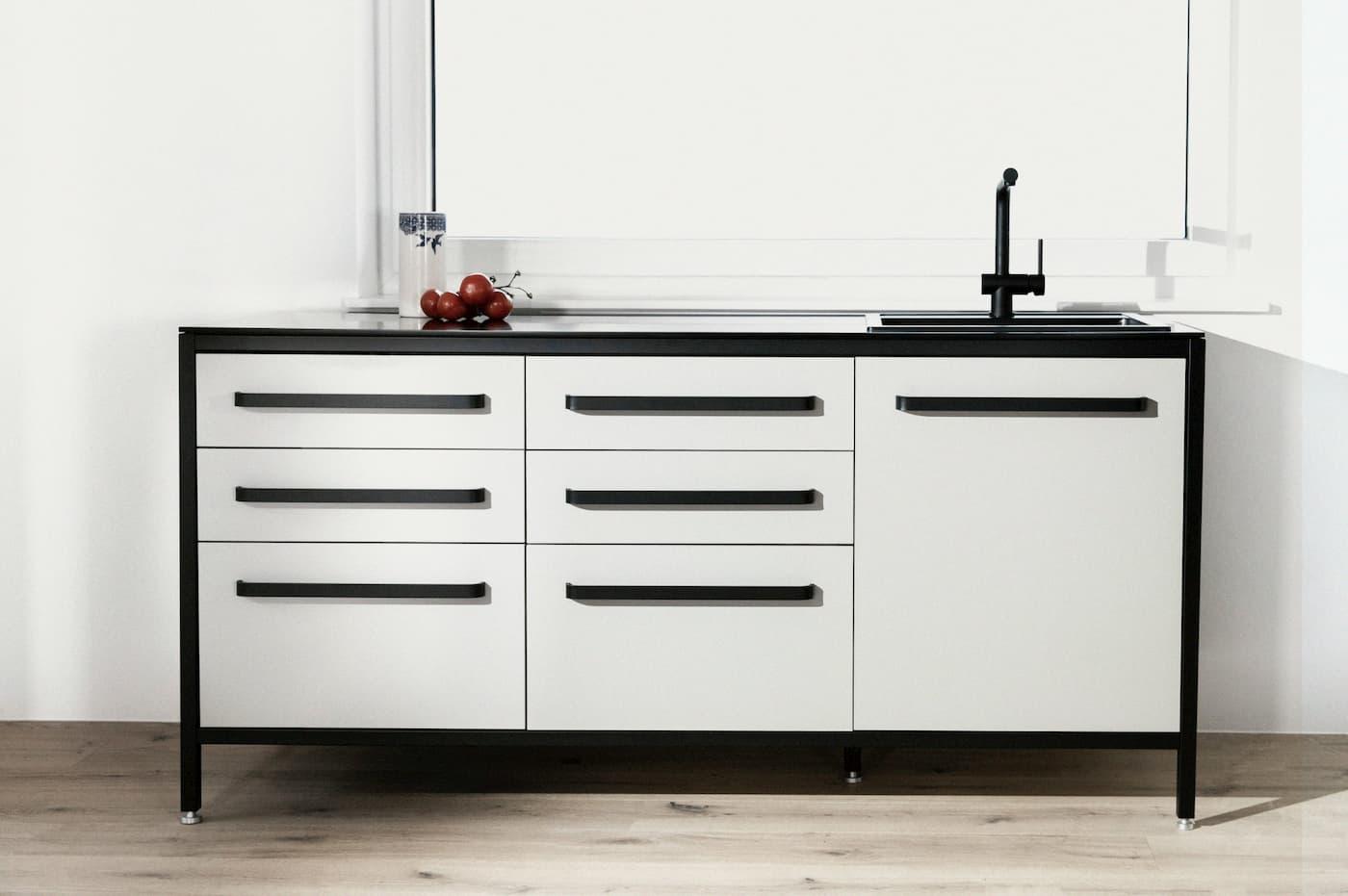 keep Küchenmodul LOW mit drei unterschiedlichen Abteilungen in grau unter einem Fenster an der Wand stehend.