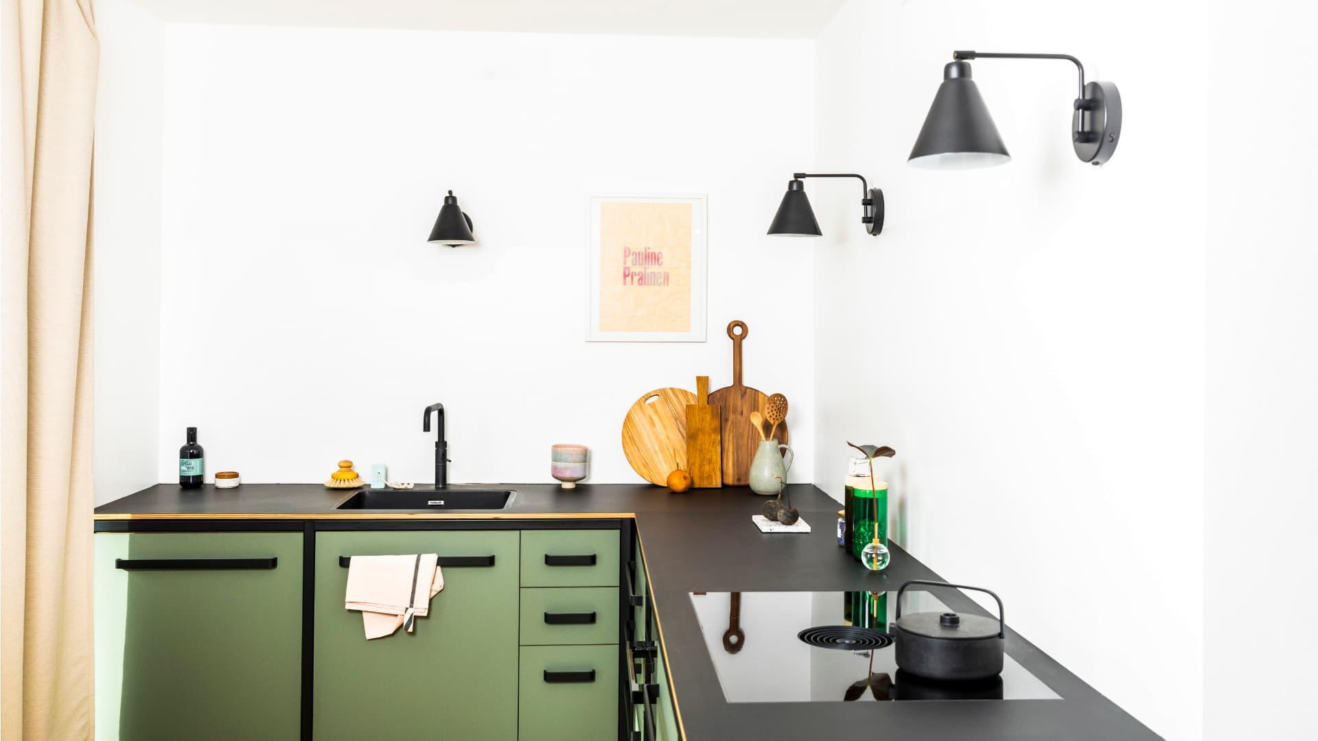 Modulküche-komplett-von-keep-in-olivegrün-mit-schwarzem-Stahlrahmen-und-Arbeitsfläche